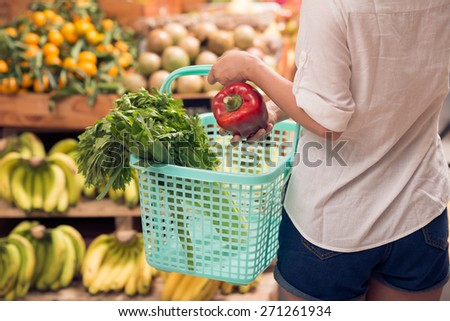 Woman choosing greens and vegetables for the salad at the market - stock photo