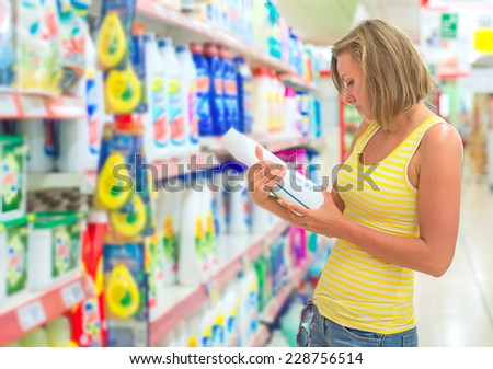 Woman choosing laundry detergent in grocery store. - stock photo
