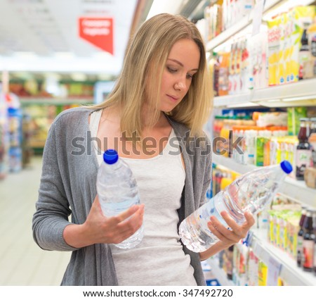 Woman choosing mineral water in grocery store. - stock photo