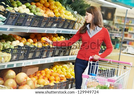 woman choosing orange or mandarin during shopping at fruit vegetable supermarket - stock photo