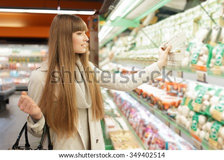 Woman choosing products at supermarket - stock photo