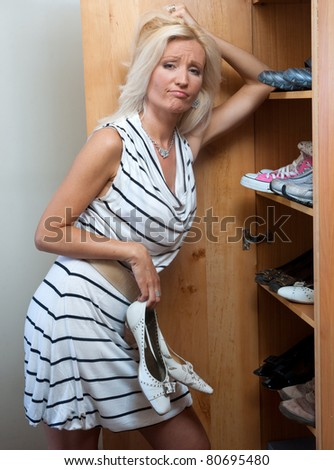 woman choosing shoes in front of open closet - stock photo