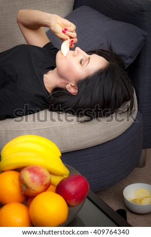 Woman choosing to eat chips and crisps instead of the fruit she has on a table which would be a healthier choice essentially  cheating and failing her diet - stock photo