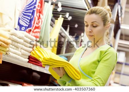 Woman choosing towels in a mega store - stock photo