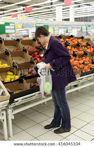 Woman choosing vegetables in a grocery store - stock photo