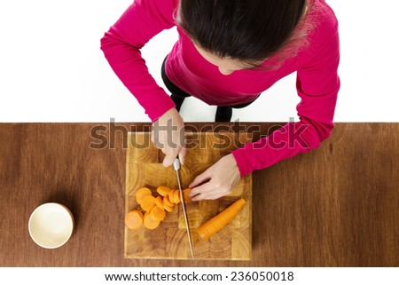 woman chopping up carrots on a wooden chopping board taken from a birds eye view from above - stock photo