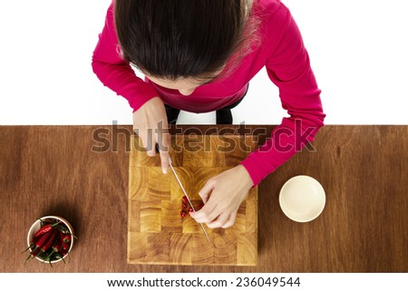 woman chopping up chillis on a wooden chopping board taken from a birds eye view from above - stock photo