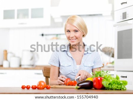 Woman chops vegetables for salad sitting at the kitchen table - stock photo