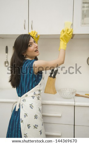 Woman cleaning a kitchen cabinet with a sponge - stock photo