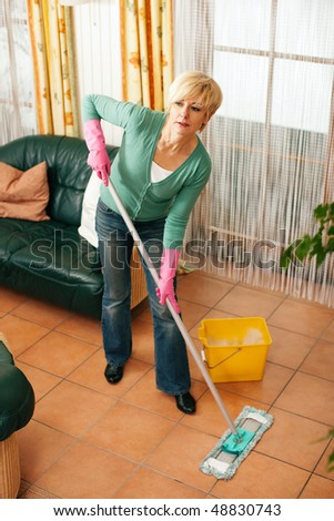 Woman cleaning and mopping the floor in her home - stock photo
