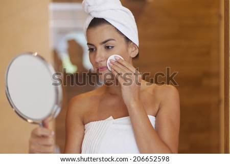 Woman cleaning face in bathroom  - stock photo