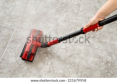 woman cleaning floor steam cleaning into the room - stock photo