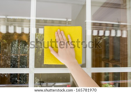Woman cleaning glass outdoor with a yellow cloth - stock photo