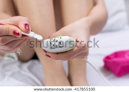 Woman cleaning her epilator device in bed