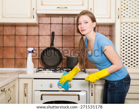 Woman cleaning house. Beautiful young housewife girl polishing oven in the kitchen. - stock photo