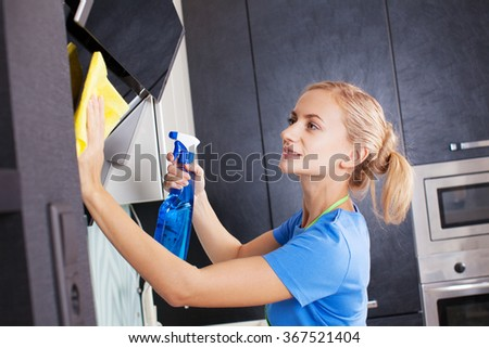 Woman cleaning kitchen. Young woman washing kitchen hood - stock photo