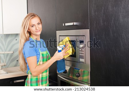 Woman cleaning microwave atkitchen. Female doing housework - stock photo
