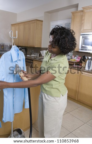 Woman Cleaning Shirt In The Kitchen - stock photo