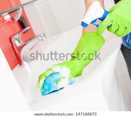 Woman cleaning sink and faucet in bathroom at home - stock photo