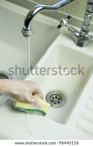 woman cleaning sink with sponge scouring pad - stock photo