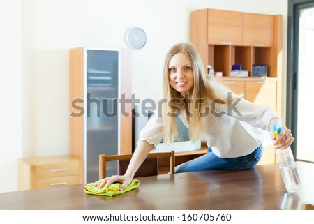 woman cleaning  table with rag and cleanser at home