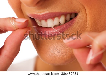 Woman cleaning teeth with dental floss for perfect hygiene and healthy teeth.