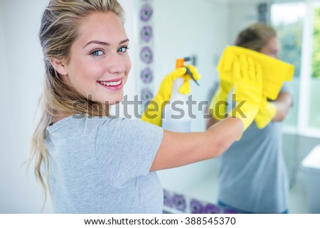 Woman cleaning the mirror in the bathroom - stock photo