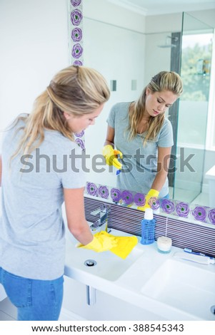 Woman cleaning the sink in the bathroom