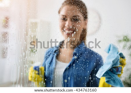 Woman cleaning window with special cleaner - stock photo