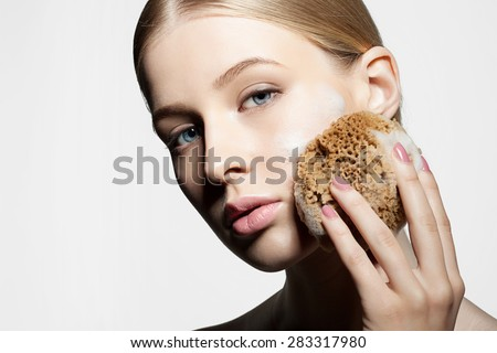 Woman cleans and exfoliates the skin with a natural sponge foam face on a white background - stock photo