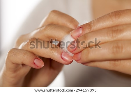 woman cleans her nail polish with a cotton