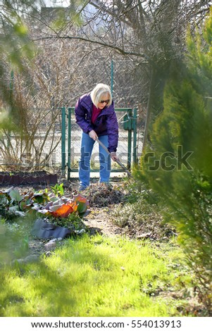Woman cleans the garden in early spring