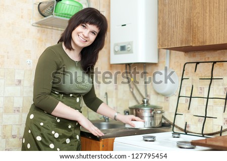 woman cleans the kitchen sink with melamine sponge - stock photo