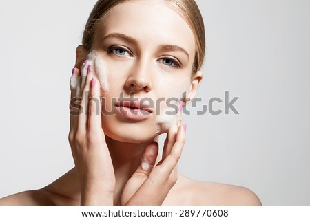 Woman clears a face skin foam on a gray background - stock photo