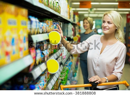 Woman clients buying infant food in jars at supermarket - stock photo