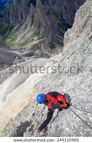 """Woman climber descending steep rock wall along the steel cable on via ferrata """"Merlone"""", Cadini di Misurina, Dolomite Alps, Italy - stock photo"""