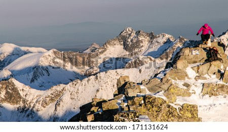 Woman climber doing acrobatic moves on the rugged summit of Rysy mountain in winter in High Tatras national park, Slovakia - stock photo