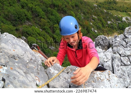 Woman climber grabs a hand hold on the rock wall - stock photo
