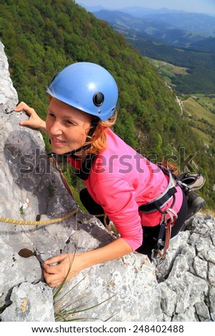 Woman climber grasping hand holds on limestone rock - stock photo