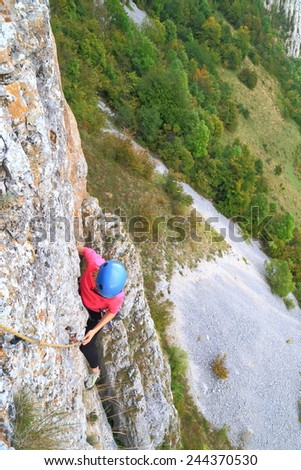 Woman climber hanging on steep wall above distant ground - stock photo