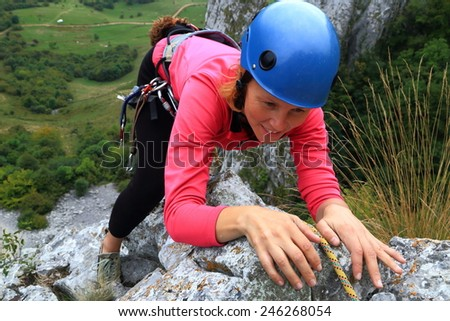 Woman climber holding on the limestone rock during climbing trip - stock photo