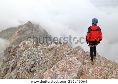 Woman climber on long ridge near Averau peak surrounded by clouds, Dolomite Alps, Italy