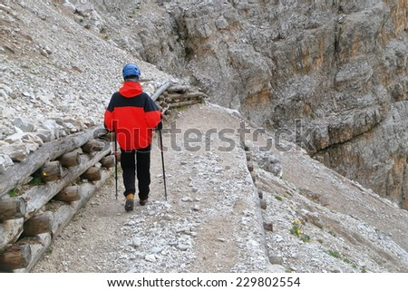 Woman climber on the road descending from Pomedes refuge, Tofana massif, Dolomite Alps, Italy