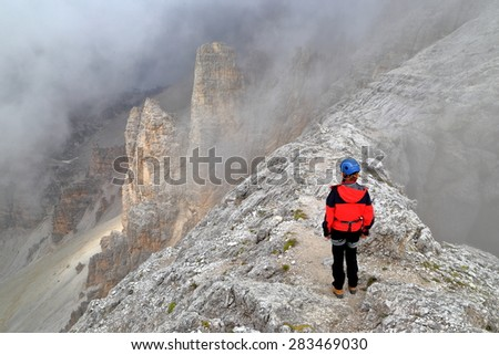 Woman climber surrounded by clouds on a rough trail across Tofana massif, Dolomite Alps, Italy - stock photo