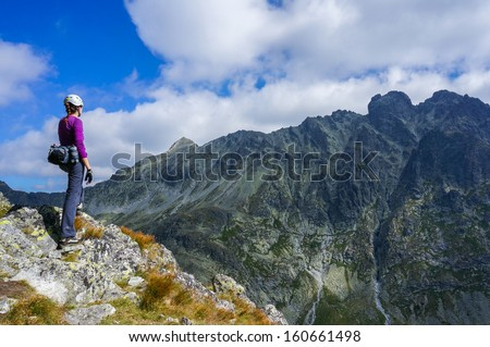 Woman climber with helmet admiring the view from the edge of a cliff in the mountains. High Tatra, Slovakia - stock photo