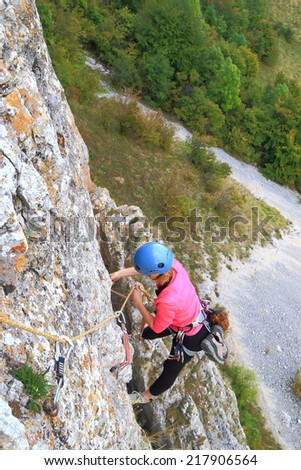 Woman climbing a steep wall high above ground - stock photo