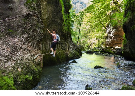 Woman climbing mountain wall over a river in a canyon - stock photo