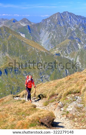 Woman climbs a sunny trail on the mountain with a backpack and walking poles - stock photo