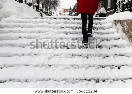 woman climbs the stairs in the snow - stock photo