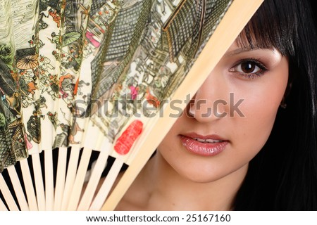 Woman closing her face with fan - stock photo